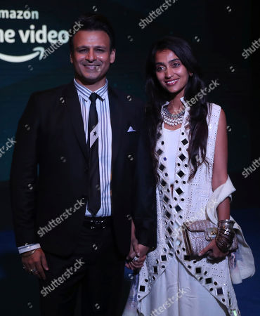 Stock Photo of Bollywood Vivek Oberoi, left, along with his wife Priyanka Alva Oberoi poses for photographs during a blue carpet event organized by Amazon Prime Video in Mumbai, India