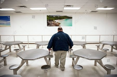 An employee walks through a cafeteria during a tour of the Stewart Detention Center, in Lumpkin, Ga. The Stewart Detention Center sits in Lumpkin, a rural town about 140 miles southwest of Atlanta and right next to the Georgia-Alabama state line. The city's 1,172 residents are outnumbered by the roughly 1,650 male detainees that U.S. Immigration and Customs Enforcement said were being held in the detention center in late November