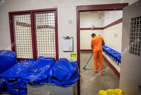 A detainee bags mops the floor at the intake station at the Stewart Detention Center, in Lumpkin, Ga. The Stewart Detention Center sits in Lumpkin, a rural town about 140 miles southwest of Atlanta and right next to the Georgia-Alabama state line. The city's 1,172 residents are outnumbered by the roughly 1,650 male detainees that U.S. Immigration and Customs Enforcement said were being held in the detention center in late November