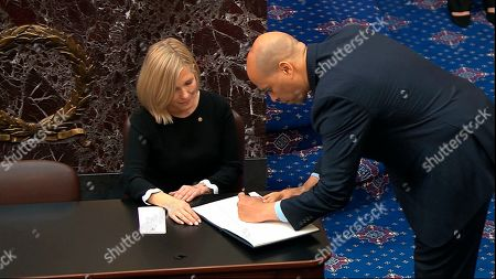 Stock Image of In this image from video, Sen. Cory Booker, D-N.J., signs the oath book after being sworn in for the impeachment trial of President Donald Trump in the Senate at the U.S. Capitol in Washington
