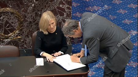 Stock Picture of In this image from video, Sen. Sherrod Brown, D-Ohio, signs the oath book after being sworn in for the impeachment trial of President Donald Trump in the Senate at the U.S. Capitol in Washington
