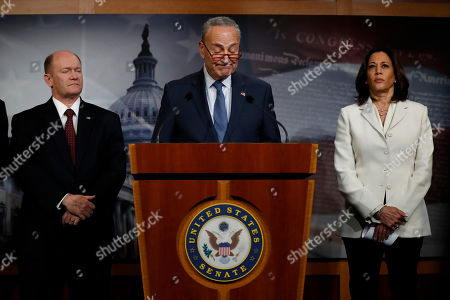 Democratic leader Sen. Chuck Schumer, D-N.Y., center, reacts while standing with Sen. Chris Coons, D-Del., left, a member of the Foreign Relations Committee, and Sen. Kamala Harris, D-Calif., a member of the Senate Judiciary Committee, during a news conference about the impeachment trial of President Donald Trump on charges of abuse of power and obstruction of Congress, at the Capitol in Washington