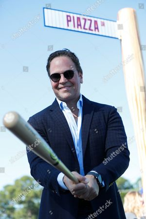 Stock Image of Former New York Mets catcher Mike Piazza poses for a photo under a street sign for the newly named Piazza Dr., after a ceremony in front of the Mets spring training facility, in Port St. Lucie, Fla