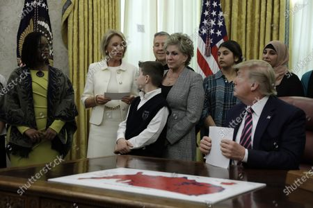 Stock Picture of US President Donald J. Trump listens to Education Secretary Betsy DeVos during the Announcement of the Guidance on Constitutional Prayer in Public Schools in the the Oval Office at the White House in Washington, DC, USA, 16 January 2020.