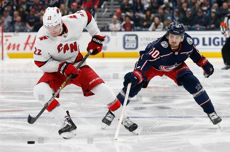 Stock Image of Carolina Hurricanes' Brett Pesce, left, hits the puck away from Columbus Blue Jackets' Alexander Wennberg, of Sweden, during the second period of an NHL hockey game, in Columbus, Ohio