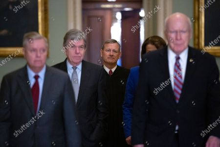Chief Justice of the United States Supreme Court John Roberts is escorted to the Senate Floor by United States Senator Lindsey Graham (Republican of South Carolina), United States Senator Roy Blunt (Republican of Missouri), United States Senator Patrick Leahy (Democrat of Vermont), and United States Senator Dianne Feinstein (Democrat of California) after arriving at the United States Capitol in Washington DC. Roberts swore Senators in as jurors in the impeachment trial.