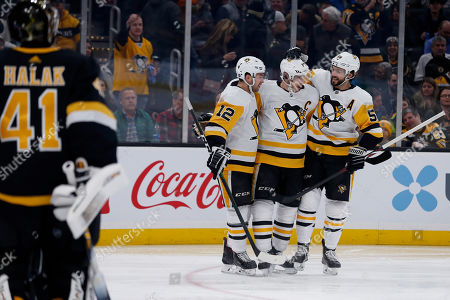 Pittsburgh Penguins center Sidney Crosby, center, is congratulated by teammates Dominik Simon (12) and Kris Letang (58) after scoring a goal against Boston Bruins goaltender Jaroslav Halak (41) during the first period of an NHL hockey game, in Boston