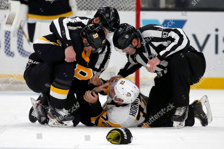 Linesman Brian Murphy (93) and linesman Matt MacPherson (83) try to break up a fight between Boston Bruins defenseman Torey Krug (47) and Pittsburgh Penguins right wing Patric Hornqvist (72) in the second period of an NHL hockey game, in Boston