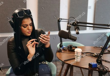 Amani Al-Khatahtbeh, founder of Muslimgirl.com, checks the notifications on her phone as she sits in a Spotify recording studio, in New York