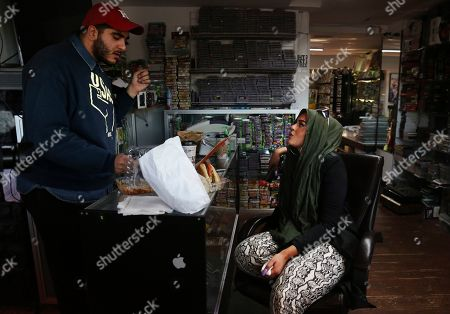 Stock Image of Amani Al-Khatahtbeh and his sister Amani al-Khatahtbeh eat breakfast together at their family electronics store after attending Friday prayer together, as they do every Friday when Amani is home, at Retros in Somerville, N.J