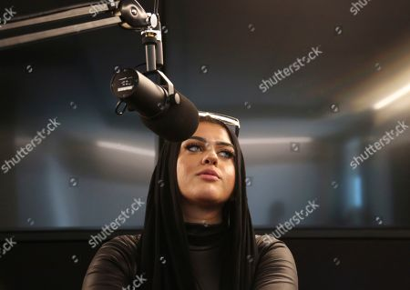 Stock Photo of Amani Al-Khatahtbeh, founder of Muslimgirl.com, sits in a Spotify recording studio as she and and a cohost record a pilot for her new potential podcast, in New York