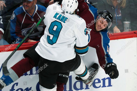 San Jose Sharks left wing Evander Kane, front, draws an interference penalty as he slams Colorado Avalanche defenseman Samuel Girard into the boards late in the third period of an NHL hockey game, in Denver. Colorado won 4-0