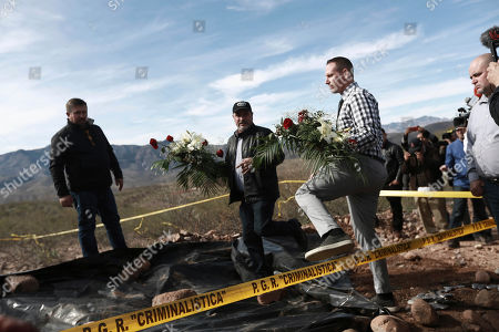 Bryan Lebaron, second from right, and relatives place flowers where one of the cars belonging to the extended LeBaron family was ambushed by gunmen last year near Bavispe, Sonora state, Mexico, . Lopez Obrador said Sunday there is an agreement to establish a monument will be put up to memorialize nine U.S.-Mexican dual citizens ambushed and slain last year by drug gang assassins along a remote road near New Mexico