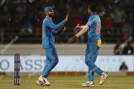 India's captain Virat Kohli, left, and Navdeep Saini celebrate the dismissal of Australia's Mitchell Starc during the second one-day international cricket match between India and Australia in Rajkot, India