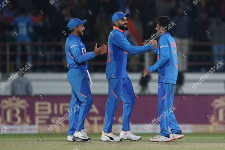 India's captain Virat Kohli, center, Yuzvendra Chahal, right, and Kuldeep Yadav celebrate their victory in the second one-day international cricket match against Australia in Rajkot, India