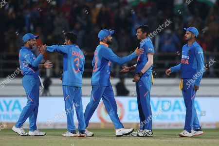 Indian cricket captain Virat Kohli, center, celebrates with teammates their victory in the second one-day international cricket match against Australia in Rajkot, India