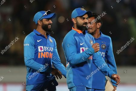 Indian cricket captain Virat Kohli, center, along with teammates celebrate their victory in the second one-day international cricket match against Australia in Rajkot, India