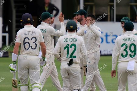 Keshav Maharaj of South Africa, centre right, is congratulated by Faf du Plessis, 2nd left, after taking the wicket of England's Jos Buttler, left, during day two of the third cricket test between South Africa and England in Port Elizabeth, South Africa