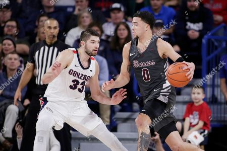 Stock Image of Santa Clara forward DJ Mitchell (0) dribbles while defended by Gonzaga forward Killian Tillie (33) during the second half of an NCAA college basketball game in Spokane, Wash