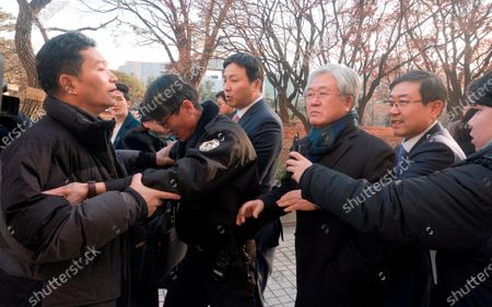 A former Samsung worker (L) protests against Park Sang-Jin (3rd R), former president of Samsung Electronics who leaves the Seoul High Court after a trial