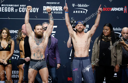 """Conor McGregor, front left, and Donald """"Cowboy"""" Cerrone pose during a ceremonial weigh-in for the UFC 246 mixed martial arts bout, in Las Vegas. The two are scheduled to fight in a welterweight bout Saturday in Las Vegas"""