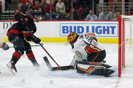 Carolina Hurricanes center Sebastian Aho, left, of Finland, misses a shot on goal against Anaheim Ducks goaltender Ryan Miller (30) during the second period of an NHL hockey game in Raleigh, N.C