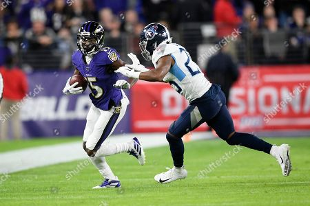 Baltimore Ravens wide receiver Marquise Brown (15) runs with the ball against Tennessee Titans cornerback Adoree' Jackson (25) during the first half an NFL divisional playoff football game, in Baltimore