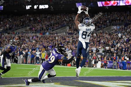 Tennessee Titans wide receiver Corey Davis (84) catches the ball for a touchdown past Baltimore Ravens free safety Earl Thomas (29) during the second half an NFL divisional playoff football game, in Baltimore