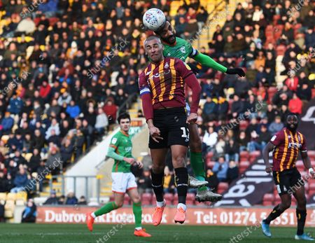 James Perch of Sculthorpe United goes up for the ball against James Vaughan of Bradford City