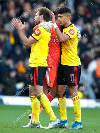 Stock Photo of Watford's Craig Dawson, left, hugs with his teammates goalkeeper Ben Foster and Watford's Adam Masina, right, at the end of the English Premier League soccer match between Watford and Tottenham Hotspur at Vicarage Road, Watford, England, . Match endedd 0-0