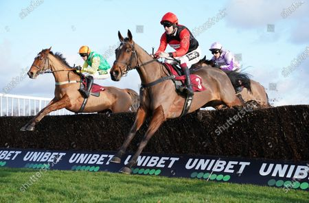 Haydock Park Racecourse The Patrick Coyne Memorial Altar Novices' Steeple Chase. Sam Brown ridden by Aidan Coleman (near) clears the final fence first time around to win, with Joke Dancer ridden by Danny Cook (yellow).