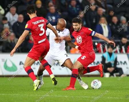 Andre Ayew of Swansea City is challenged by Antonee Robinson and Sam Morsy of Wigan Athletic