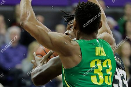 Washington forward Isaiah Stewart, center, eyes the basket as Oregon forward Francis Okoro, right, defends, during the first half of an NCAA college basketball game, in Seattle