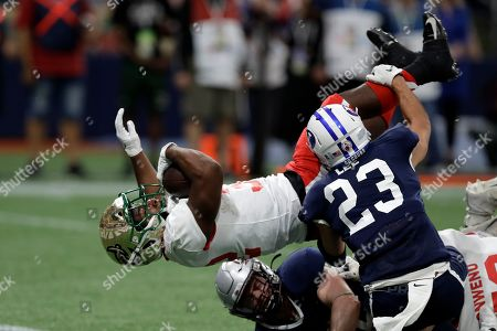 Stock Photo of Benny LeMay, Austin Lee. East running back Benny LeMay, of Charlotte, (32) gets flipped by West safety Austin Lee, of BYU, (23) as he scores during the first half of the East West Shrine football game, in St. Petersburg, Fla