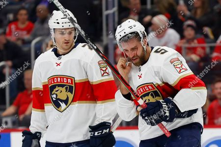 Florida Panthers defenseman Aaron Ekblad (5) skates to the bench while bleeding after being high-sticked, as Josh Brown looks on during the first period of the team's NHL hockey game against the Detroit Red Wings, in Detroit