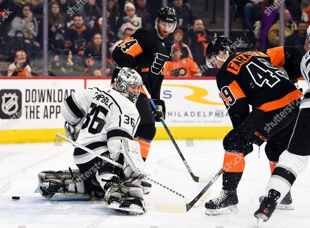 Los Angeles Kings goaltender Jack Campbell, left, is unable to make a save on a goal scored by Philadelphia Flyers' Joel Farabee (49) as Sean Couturier, center, looks on during the second period of an NHL hockey game, in Philadelphia