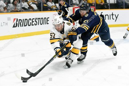 Nashville Predators defenseman Dante Fabbro (57) and Buffalo Sabres right wing Kyle Okposo (21) reach for the puck during the first period of an NHL hockey game, in Nashville, Tenn