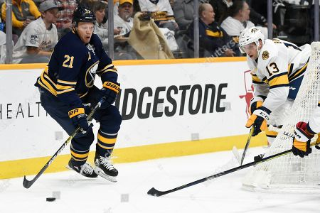 Buffalo Sabres right wing Kyle Okposo (21) gets control of the puck in front of Nashville Predators center Nick Bonino (13) during the first period of an NHL hockey game, in Nashville, Tenn