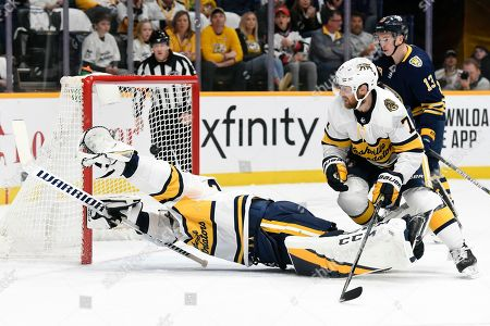 Buffalo Sabres right wing Kyle Okposo scores past Nashville Predators goaltender Pekka Rinne (35), of Finland, and defenseman Yannick Weber (7), of Switzerland, during the first period of an NHL hockey game, in Nashville, Tenn