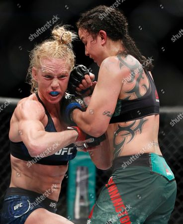 Holly Holm, left, fights Raquel Pennington during a UFC 246 women's bantamweight mixed martial arts bout, in Las Vegas