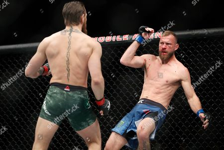 """Donald """"Cowboy"""" Cerrone falls after being hit by Conor McGregor during a UFC 246 welterweight mixed martial arts bout, in Las Vegas"""