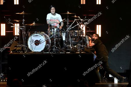 Blink-182, Travis Barker. Travis Barke, left, drummer of the rock band Blink-182 performs live on stage as a photographer takes a close photo of him at the 2020 iHeartRadio ALTer Ego at the Forum, in Inglewood, Calif