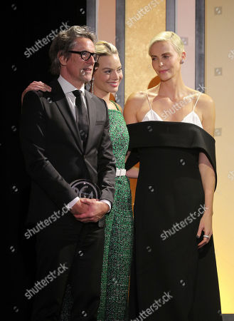 Charles Randolph, Margot Robbie, Charlize Theron. Margot Robbie, center, presents Charles Randolph, left, and Charlize Theron, right, with the Stanley Kramer Award at the 31st Annual Producers Guild Awards at the Hollywood Palladium, in Los Angeles