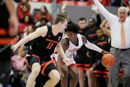 Washington State guard Noah Williams, right, dribbles while pressured by Oregon State guard Zach Reichle during the second half of an NCAA college basketball game in Pullman, Wash