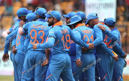 India's captain Virat Kohli, center, and teammates stand in a huddle before the start of the third and final one-day international cricket match between India and Australia in Bangalore, India