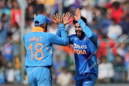 Ravindra Jadeja, Virat Kohli. India's Ravindra Jadeja, right, celebrates with captain Virat Kohli the dismissal of Australia's Mitchell Starc during the third one-day international cricket match between India and Australia in Bangalore, India