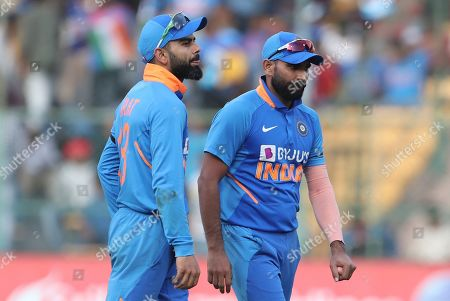Virat Kohli, Mohammed Shami. India's captain Virat Kohli, left, and Mohammed Shami leave the field at the end of Australian innings during the third one-day international cricket match between India and Australia in Bangalore, India