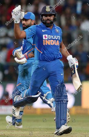 Rohit Sharma, Virat Kohli. India's Rohit Sharma, front, and captain Virat Kohli run between the wickets to score during the third one-day international cricket match between India and Australia in Bangalore, India