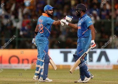 Rohit Sharma, Virat Kohli. India's Rohit Sharma, right, celebrates with captain Virat Kohli after hitting a boundary during the third one-day international cricket match between India and Australia in Bangalore, India