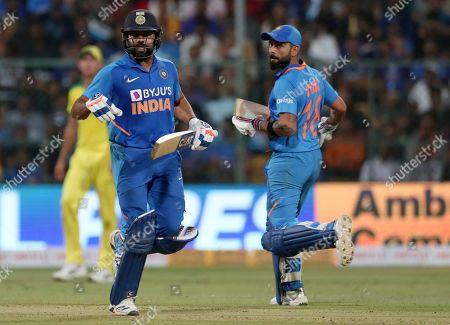 Virat Kohli, Rohit Sharma. India's captain Virat Kohli, right, and Rohit Sharma run between the wickets to score during the third one-day international cricket match between India and Australia in Bangalore, India